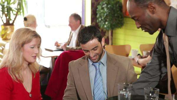 Happy couple in cafe restaurant with waiter and other customers Royalty-free stock video