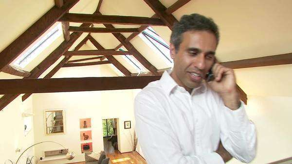 Attractive Indian businessman makes a phone call from his home Royalty-free stock video