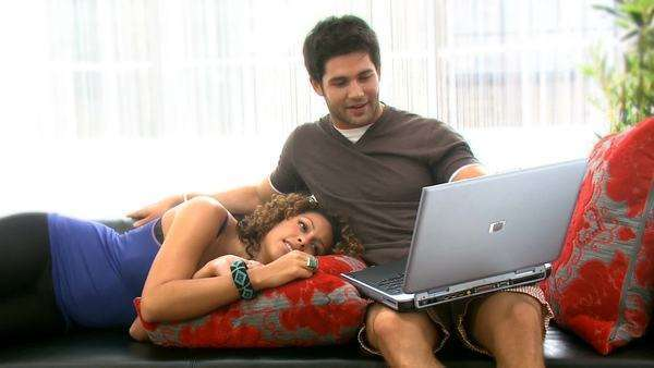 Attractive young couple with modern lifestyle relaxing together and social networking on a laptop in their contemporary home Royalty-free stock video