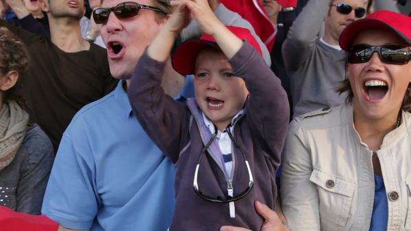 Boy with family in crowd of sports spectators Royalty-free stock video