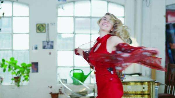 Blonde woman in a red dress is spinning and dancing round her apartment Royalty-free stock video