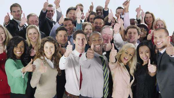 Portrait of a large group of happy and diverse business people who are standing together, isolated on white in a studio shot. They hold their thumbs up to camera to celebrate their business success. Royalty-free stock video