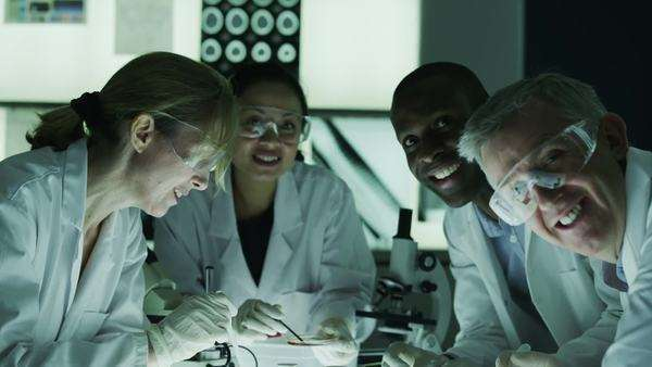 Portrait of happy team of scientists or researchers working together in a dark laboratory. In slow motion. Royalty-free stock video