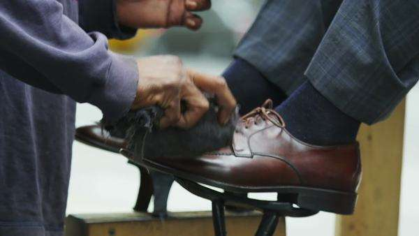 A businessman or tourist gets his shoes shined on a street in New York. No faces can be seen. In slow motion. Royalty-free stock video
