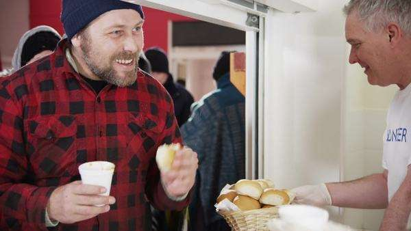 Friendly voluntary workers standing at a soup kitchen serving hatch are handing out cups of hot soup and bread to a waiting line of homeless and needy people. Royalty-free stock video