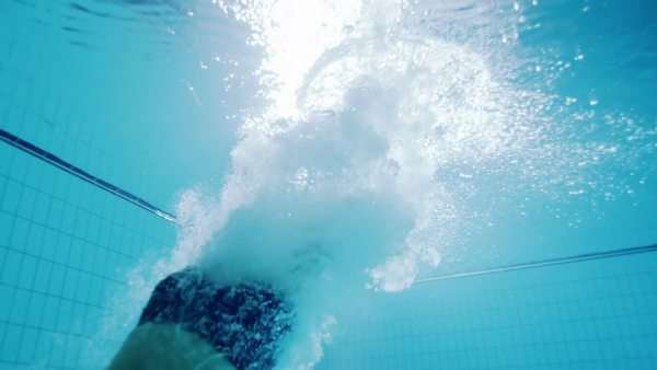 Underwater view of a professional male swimmer diving into clear blue water. Royalty-free stock video