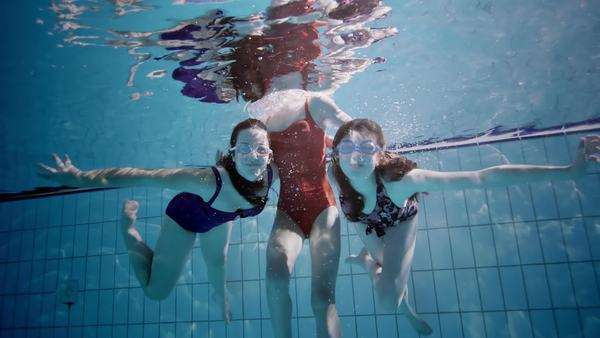 Young female friends in a swimming pool having fun together underwater and blowing kisses to the camera. Royalty-free stock video