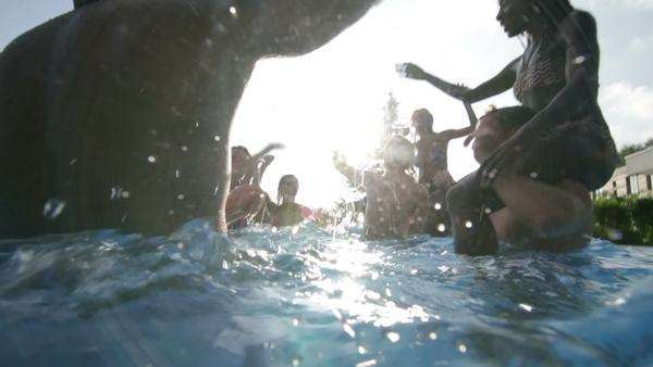 Happy fun loving group of friends playing in the water at summer pool party Royalty-free stock video
