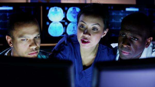 Mixed ethnicity group of medical professionals working late at night are looking at a computer screen and discussing what they see. In slow motion. Royalty-free stock video