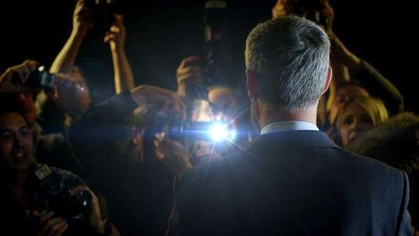 Politician or statesman at a press conference, in front of the flashing bulbs of paparazzi photographers. In slow motion. Royalty-free stock video