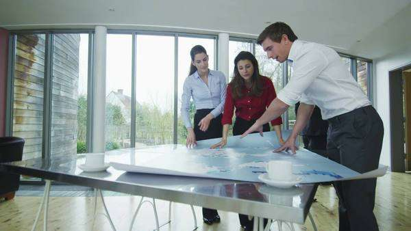 Confident group of young professionals in a meeting. They are looking at a map of the world and discussing their business strategy. Royalty-free stock video