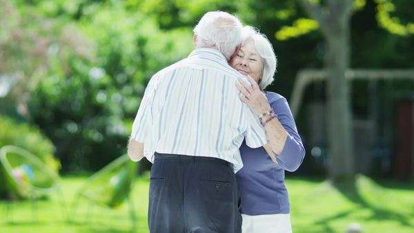 Romantic senior couple show they are still young at heart as they dance together outdoors on a summer day. Royalty-free stock video
