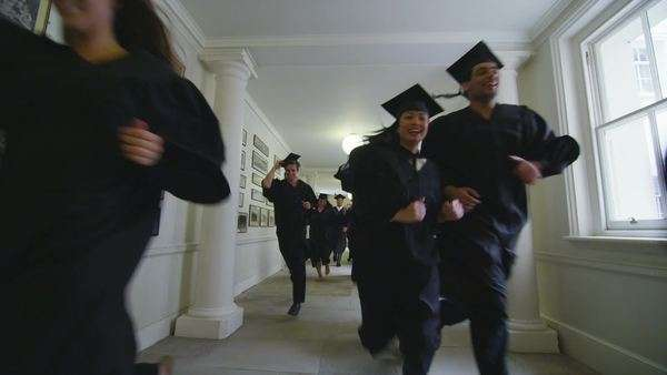 Excited mixed ethnicity group of university students on graduation day, running through the hallway of the university building dressed in caps and gowns. In slow motion. Royalty-free stock video