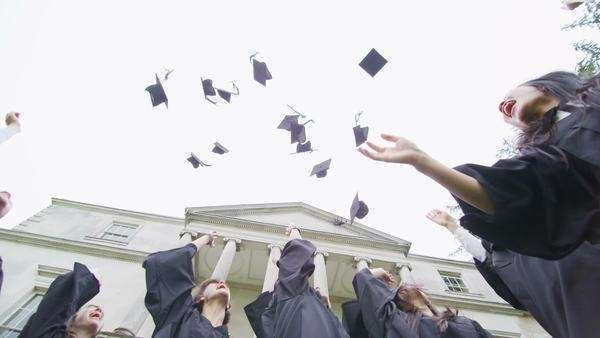 Low angle view of a happy group of student friends together outdoors on graduation day. They huddle together in a circle and throw their caps into the air. Royalty-free stock video
