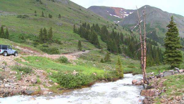 A jeep drives through wilderness in the Colorado Rockies. Royalty-free stock video