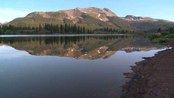 The Rocky Mountains are perfectly reflected in an alpine lake. Royalty-free stock video