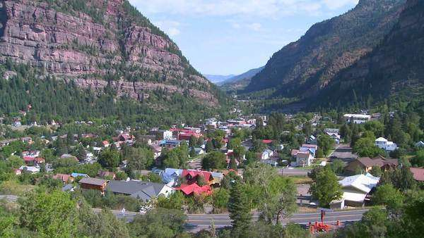 A downtown establishing shot of Ouray, Colorado with steam train passing. Royalty-free stock video