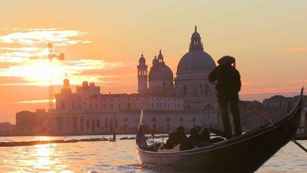 A gondola is rowed by a gondolier in front of the setting sun in romantic Venice, Italy. Royalty-free stock video