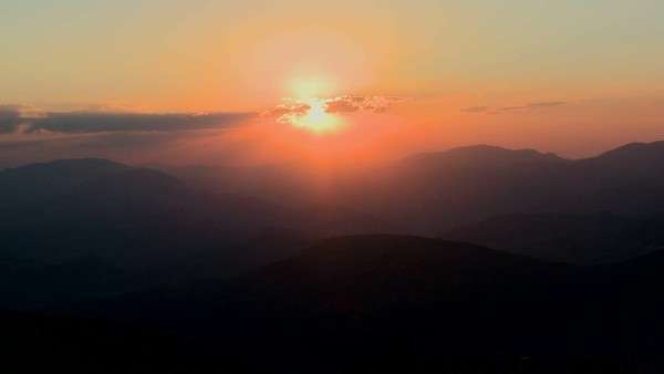Medium-shot of a fiery sunset over a generic mountain range. Royalty-free stock video
