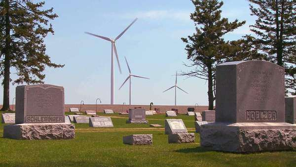 Giant windmills in the distance generate power behind farms in the American Midwest. Graveyard or cemetery foreground. Royalty-free stock video