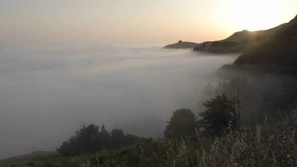 Timelapse of sun setting over fog rolling against the mountains at Big Sur, California. Royalty-free stock video
