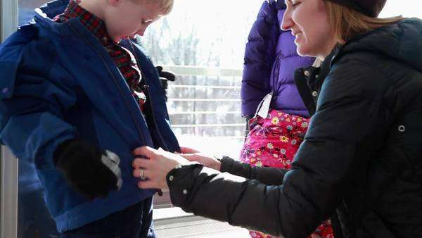 Mother helping son get dressed into winter clothing Royalty-free stock video