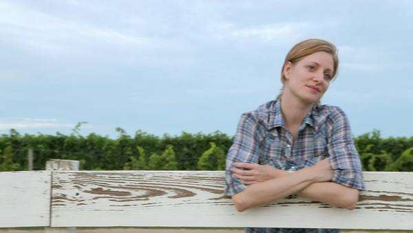 Cheerful woman leaning on fence on ranch Royalty-free stock video