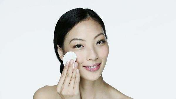 Young woman cleansing her face with cotton pad Royalty-free stock video