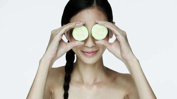 Young woman holding cucumber slices over eyes Royalty-free stock video