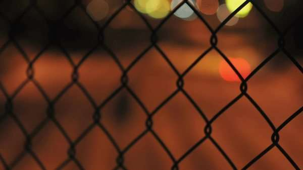 Timelapse of urban night traffic looking through a chain link fence Royalty-free stock video