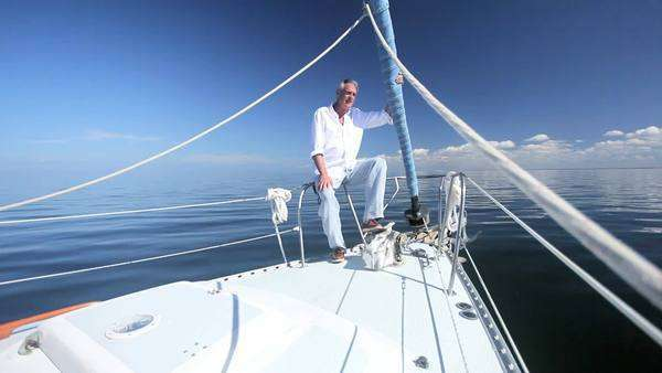 Healthy retired male enjoying his success sitting aboard his luxury sailing boat Royalty-free stock video