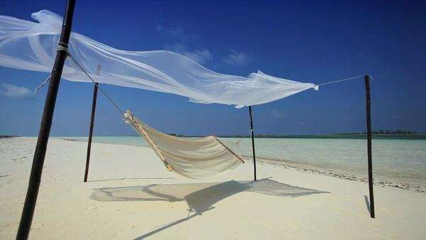 Hammock swaying over white sands of a luxury hideaway island location Royalty-free stock video