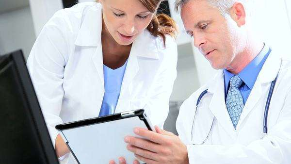 Caucasian doctors looking wireless tablet information  clinic office Royalty-free stock video
