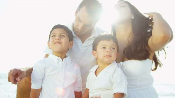 Happy Latin American parents enjoying summer time with little children by ocean sun lens flare shot on RED EPIC Royalty-free stock video