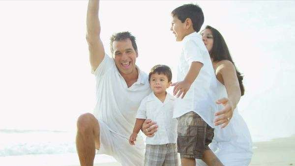 Happy Latin American family embracing together by ocean shot on RED EPIC Royalty-free stock video