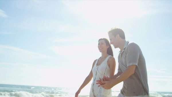 Loving young Caucasian couple holding hands walking together beach shot on RED EPIC Royalty-free stock video
