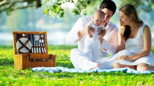 Young Caucasian parents sitting outdoors on the grass spending time with  their young baby girl shot on RED EPIC Royalty-free stock video