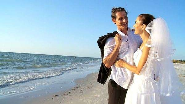 Bride & bridegroom on the beach after their wedding ceremony filmed at 60FPS Royalty-free stock video