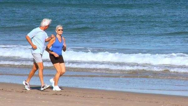 Healthy senior couple keeping fit in their retirement jogging on the beach filmed at 60FPS Royalty-free stock video