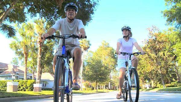 Senior couple keeping fit in their retirement on their bicycles in the sunshine on suburban roads Royalty-free stock video