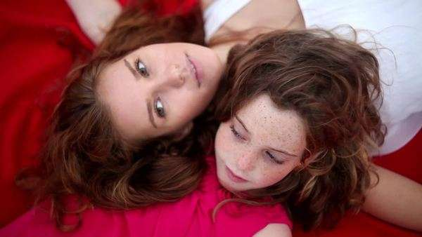 Close-up of mother and daughter's faces lying together on blanket Royalty-free stock video
