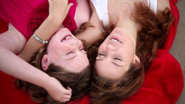 Pretty mother and daughter lying on red blanket with heads together Royalty-free stock video