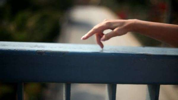 Woman's fingers walking along cement railing and making wave motions Royalty-free stock video