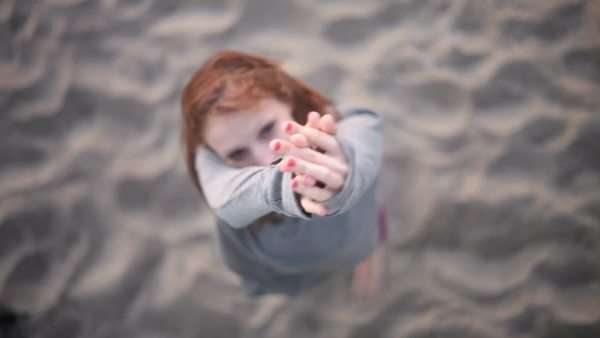 View from above of pretty redhead making hand gestures on beach Royalty-free stock video