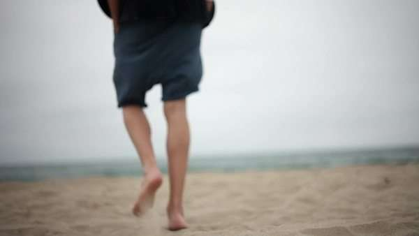 Rearview of young man walking on sand to waterfront and sitting down Royalty-free stock video