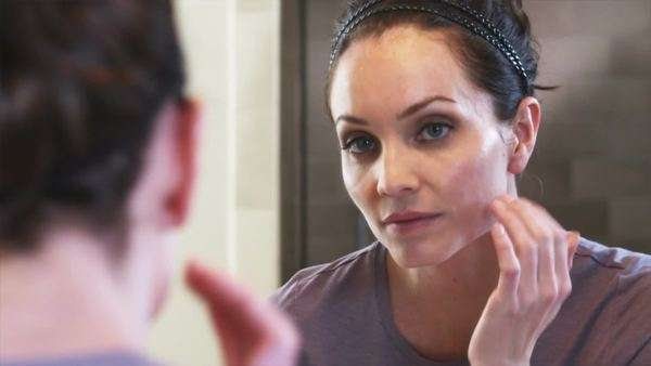 Close-up of a woman applying cream to her face as she looks in the mirror. Royalty-free stock video