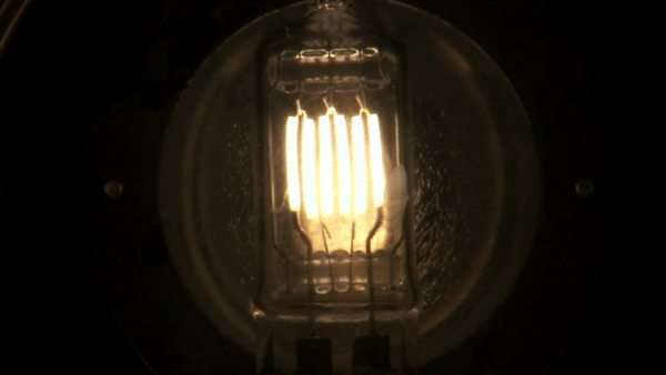 A close up of a light bulb with several filaments fading on, then fading off. Royalty-free stock video