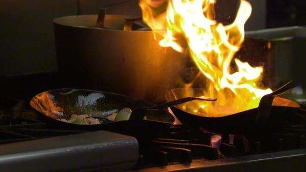 Close up slow motion of a chef cooking over an open flame in a nice restaurant in Salt Lake City, UT Royalty-free stock video