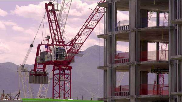 Medium shot of a tower crane rotating next to a skyscraper under construction in Salt Lake City, Utah. Royalty-free stock video