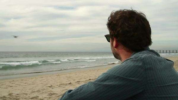 Close up of a man sitting on the beach, watching the Pacific Ocean. Royalty-free stock video
